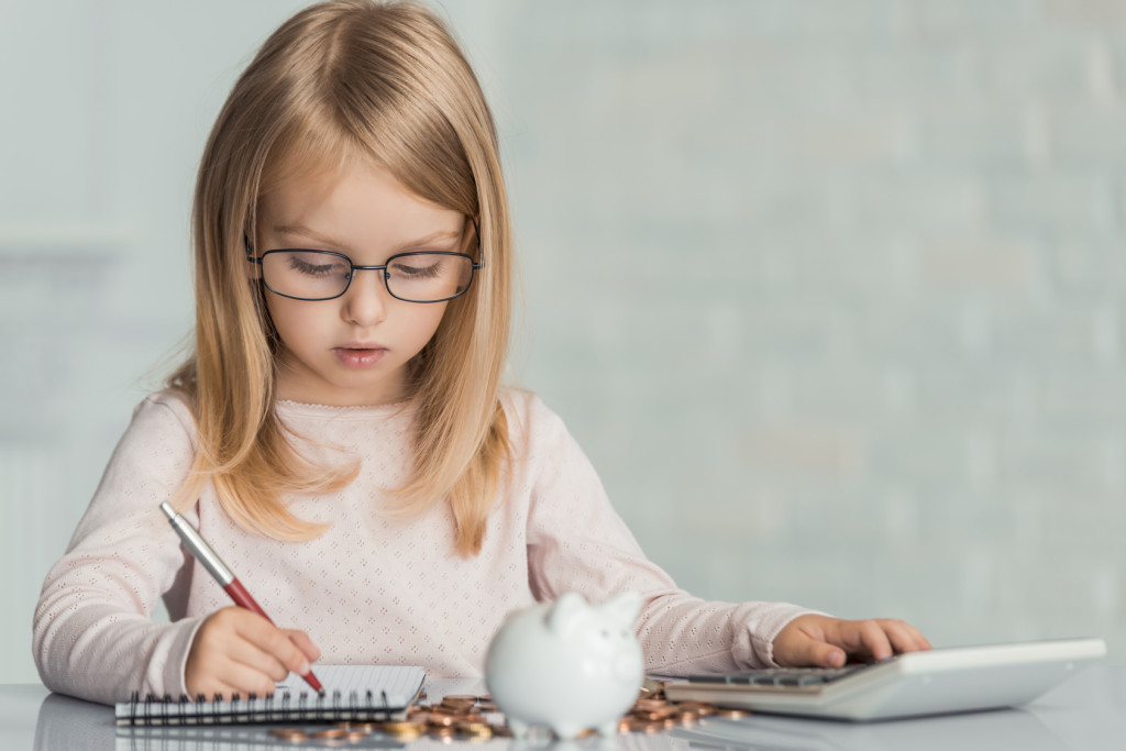 Little girl wearing eyeglasses writes in notebook at table witj calculator , coins and piggy bank