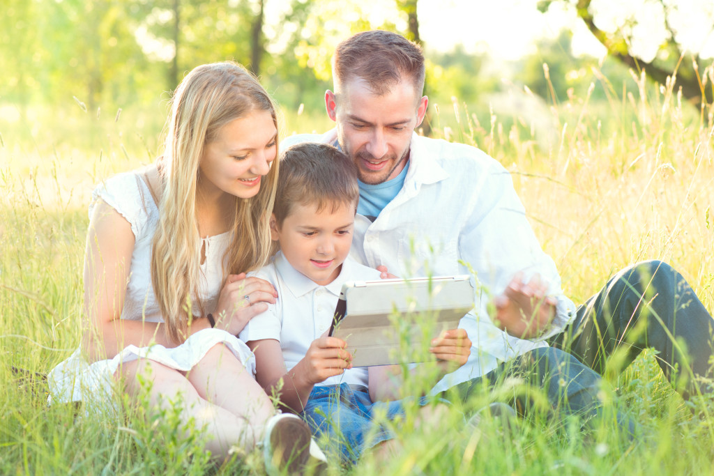 Young family with kid using tablet pc in summer park